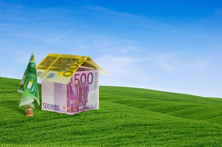 House built with banknotes lying between green hills. Conceptual image that represents the home loan Stock Photo