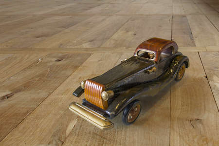 Ancient wooden toy car on background wood