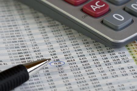 Closeup of a stock magazine with ballpen and calculator photo
