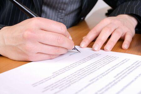 finanzen: Nahaufnahme einer Hand, die einen Vertrag unterschreibt