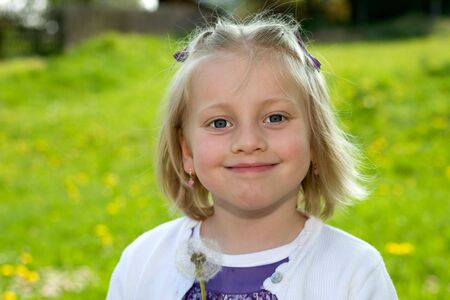 nahaufnahme: Kind im freien auf der Wiese mit Pusteblume