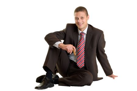 supervisory: Businessman sits relaxed on floor with cuban cigar in his hand on white background