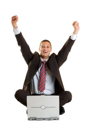 Cheering Businessman sitting on floor in front of his laptop photo