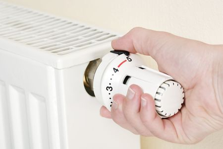 economise: Close-up of a hand holding thermostat in full position