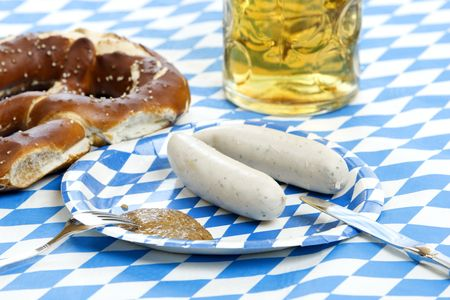 Close-up at typical Oktoberfest food with pretzel, beer stein (mug), mustard and weisswurst