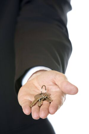businessmans hand holding key in hand ready for handing over photo