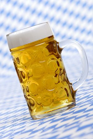 Close-up of original Bavarian Oktoberfest Beer stein called Mass full of beer with foam crown