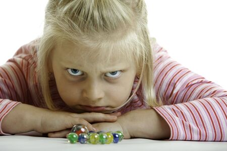 bluster: child (girl) is lying on the floor and looks angry into camera on white background