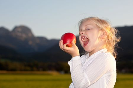 Child is holding a red apple and close to make a bite. Mountain in background