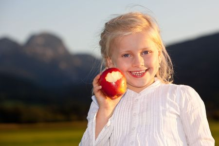 Child is holding a red apple and close to make a bite. Mountain in background Stock Photo - 5598825