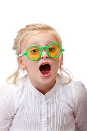 little girl surprised: Child wears green glasses and screams into camera. Isolated on white background.