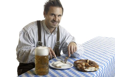 stein: Bavarian Guy is sitting at table and having a typical Oktoberfest meal with pretze (Brezn), veil sausage (Weisswurst), beer at beer stein (Mass).