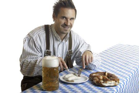sausages: De Baviera Guy est� sentado a la mesa y tener una comida t�pica con pretze Oktoberfest (Brezn), salchichas velo (Wei�wurst), la cerveza en jarra de cerveza (de comunicaci�n).