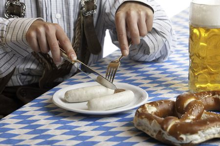 suspender: Bavarian man dressed in traditional leather trousers (lederhosen) is eating a veil sausage (Weisswurst). Stock Photo