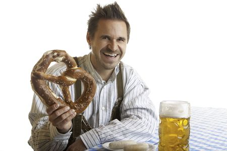 stein: Bavarian Man is sitting on bench and holding in his hand an Oktoberfest Pretzel. Beside him is a full Beer Stein (Mass). Stock Photo