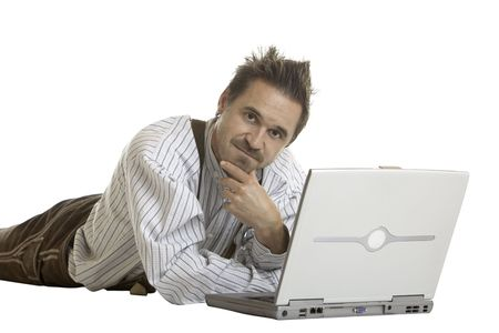 Bavarian man dressed with leather trousers (Lederhose) is lying on floor and looks con contemplative while working with laptop Stock Photo - 5598696
