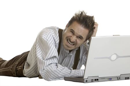 Bavarian Man dressed with leather trousers (lederhose) is lying on floor and has no idea how to work with laptop Stock Photo - 5598800