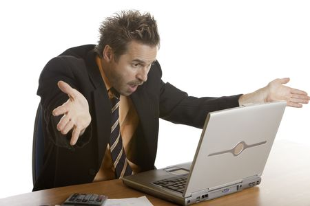 quite: Businessman sitting on his desk and is quite angry on his laptop because of a computer crash Stock Photo