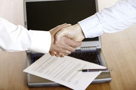 Business handshake with computer, contract and pen in background Stock Photo - 5598188