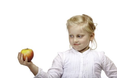 inquiring: Child is holding a red apple and close to make a bite. Mountain in background