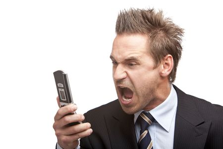 Closeup of stressed businessman holding a mobile phone and screams into it. Isolated on white background photo