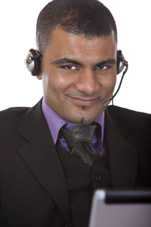 call center agent: Call center agent indossando un auricolare e seduto davanti al suo computer portatile. Isolated on white.