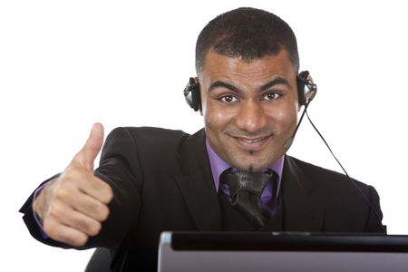 Call center agent wearing a headset and expressing happiness by showing thumb up. Stock Photo - 5707294