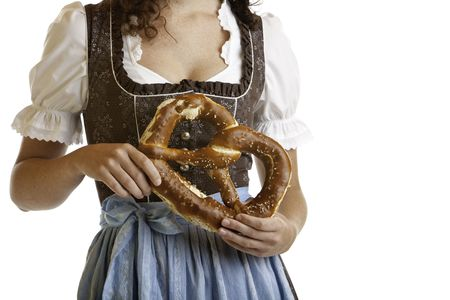 Closeup of a Bavarian girl holding a Oktoberfest Pretzel in front of her chest. Isolated on white. photo