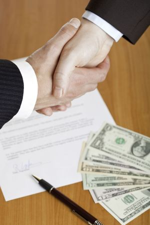 Closeup of shaking hands with contract, money and pen in background.