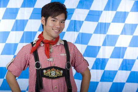 Asian Boy, dressed with Bavarian Lederhose smiles. In background Bavarian Flag visible. photo