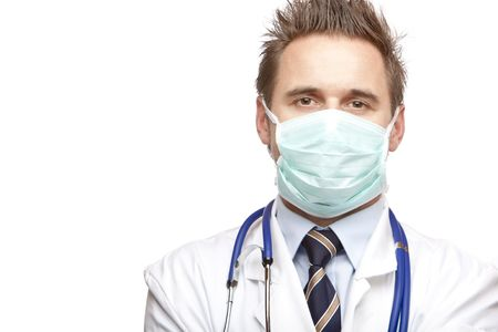 maladies: Standing medical doctor with mask and stethoscope looks self confident into camera. Isolated on white. Stock Photo