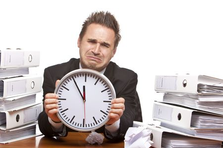 Young businessman is sitting on desk and crying because of unmanageable work and time pressure. Isolated on white. Stock Photo - 5978761