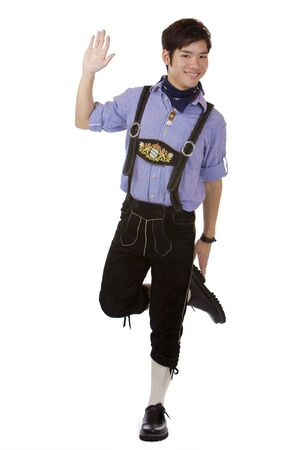 wiesn: Asian man dressed in Oktoberfest leather trousers (Lederhose) is doing the traditional Bavarian dance called