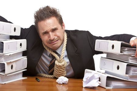 Young businessman is sitting on desk and crying because of unmanageable work. Isolated on white. Stock Photo - 6057425