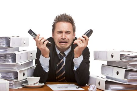 tension: Young businessman is sitting on desk, holding two telephones and crying because of unmanageable work. Isolated on white.