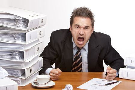 Young businessman is sitting on desk and screaming because of unmanageable work. Isolated on white. Stock Photo - 6057453