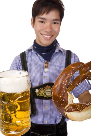 Happy man holding an Oktoberfest beer stein and pretzel into camera and smiles. Isolated on white. photo