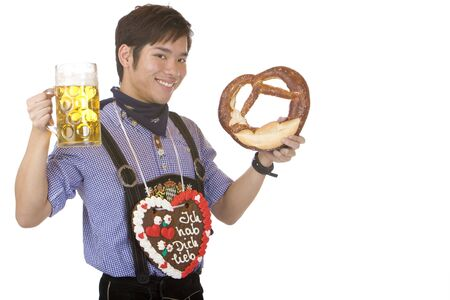 Young Asian man having gingerbread heart around neck and holds beer stein and Pretzel. Isolated on white. photo
