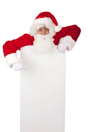 Santa Claus points on Christmas advertisment offer. Isolated on white. photo