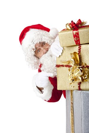 Santa  Claus is hiding behind a stack of Christmas gift boxes and points on them. Isolated on white. Stock Photo