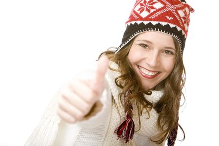 Young woman wearing cap and scarf shows thumb. Isolated on white. photo