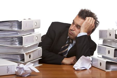 Young businessman is sitting on desk and looks frustrated on folder stack , becuase of unmanageable work. Isolated on white. Stock Photo - 6309635
