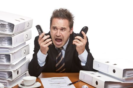 Young businessman is sitting on desk betweent folder stacks and screams into two telephones.  Isolated on white. photo