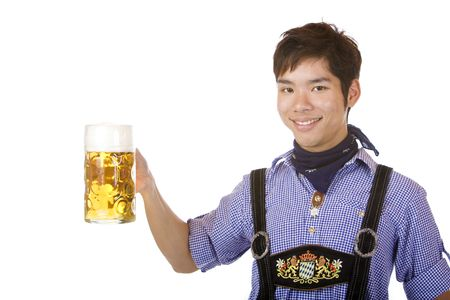 Asian Boy is holding a full Oktoberfest beer stein and smiles happy in camera. Isolated on white. photo