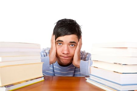 Young handsome student sitting on a desk between study books and looks frustrated. Isolated on white. Stock Photo - 6371381