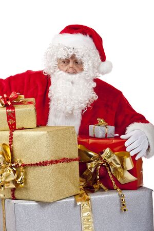 nikolaus: Santa Claus is kneeing on the floor behind a stack of Christmas gifts and looks surprised. Isolated on white.
