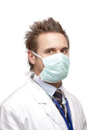 Standing medical doctor with mask and stethoscope looks self confident into camera. Isolated on white. photo