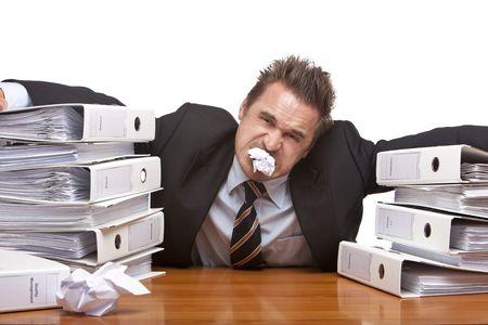 인내: Young businessman is sitting on desk and having paper sheet in his mouth, because of unmanageable work. Isolated on white.