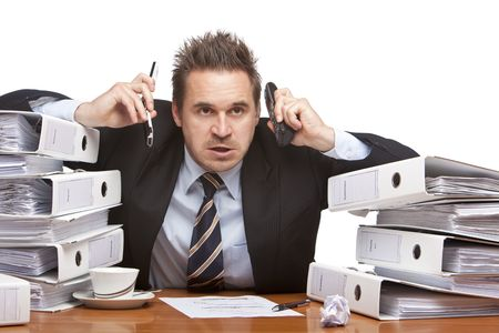 preoccupation: Young businessman is sitting on desk betweent folder stacks and having two telephones on his ears.  Isolated on white. Stock Photo