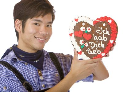 suspender: Asian man, dressed with Bavarian Lederhose holds an Oktoberfest gingerbread heart in camera and gives a kiss. Isolated on white. Stock Photo